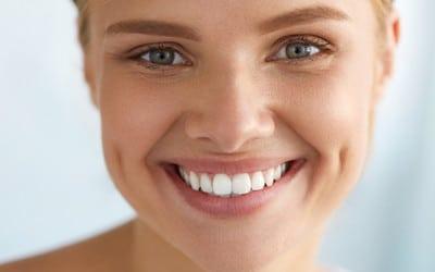 Happy female lady showing her tooth veneer